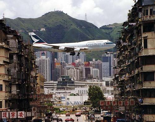 Avião pousando em meio a uma cidade