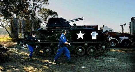 Tanque de Sydney com dois policiais andando do lado