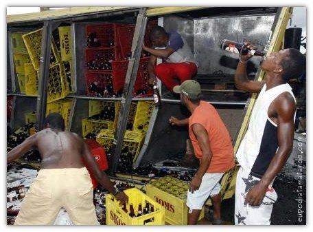Moradores dão um ajuda para descarregar cervejas e refrigerantes de caminhão que tombou