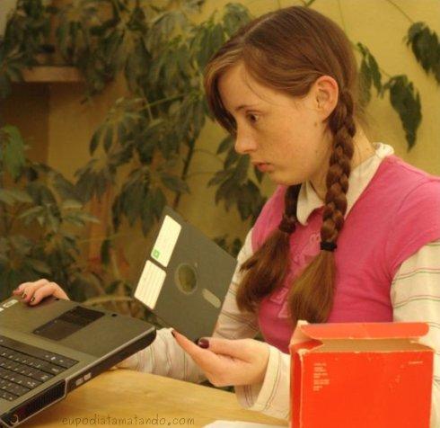 Where is your god now? hehehehe menina com disquete na mão em frente a um notebook